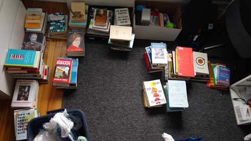 Many books, sitting in piles on the floor
